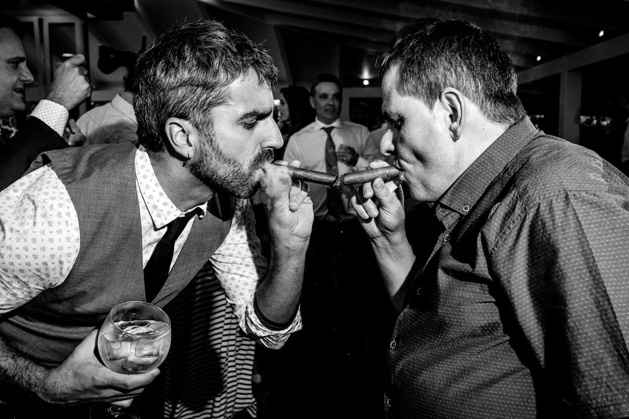 Invitados fumando puro en fiesta de boda