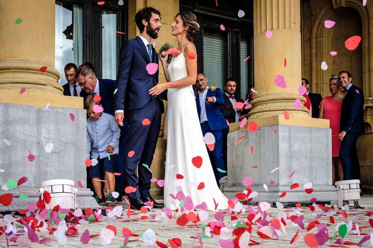Novios y pétalos de flores en boda en ayuntamiento de donostia