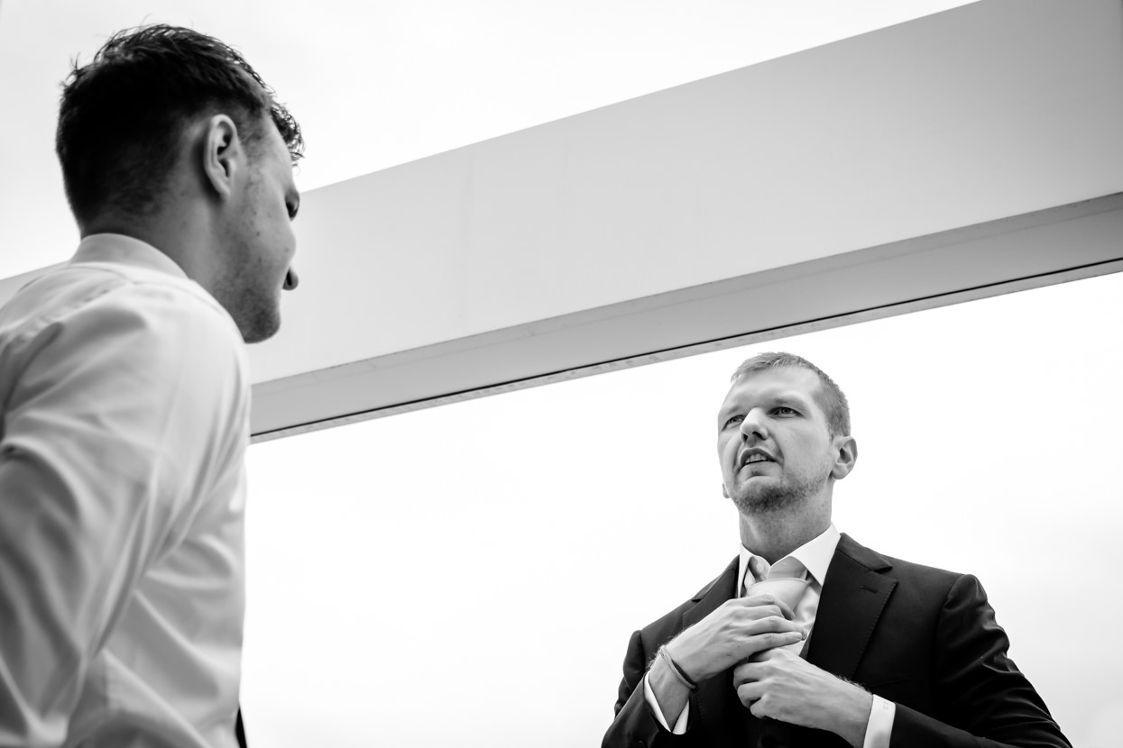 Preparativos del novio ajustando corbata. Destination wedding photographer in San Sebastian