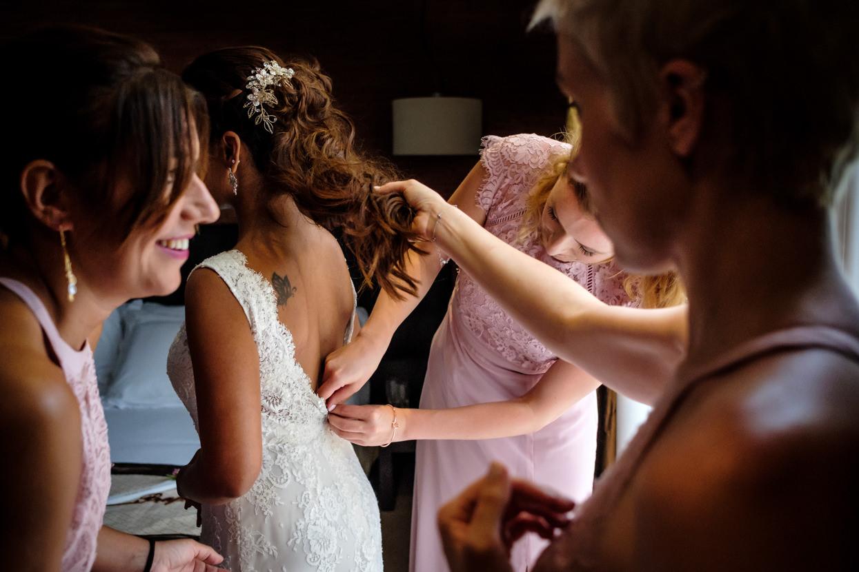 Preparativos. Amigas ajustan vestido de novia.