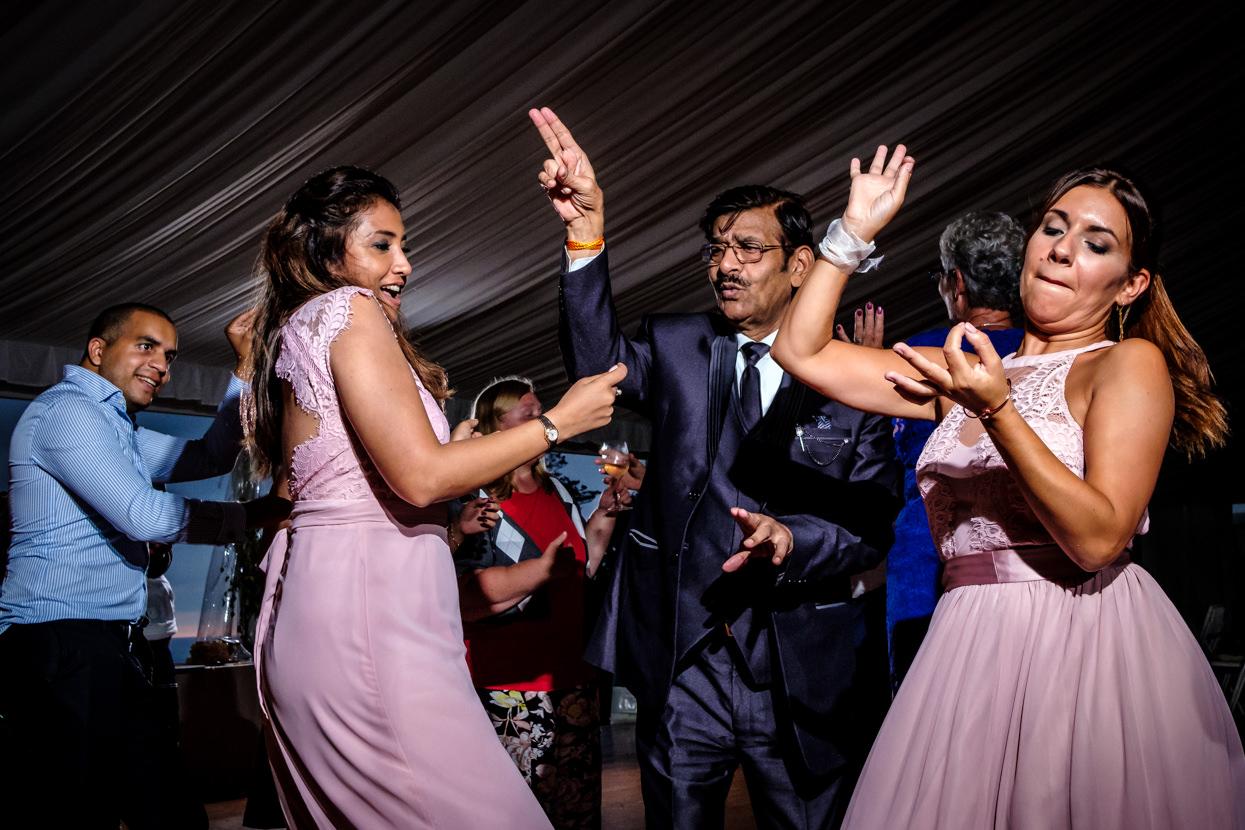 Padre de la novia baila con invitadas de boda