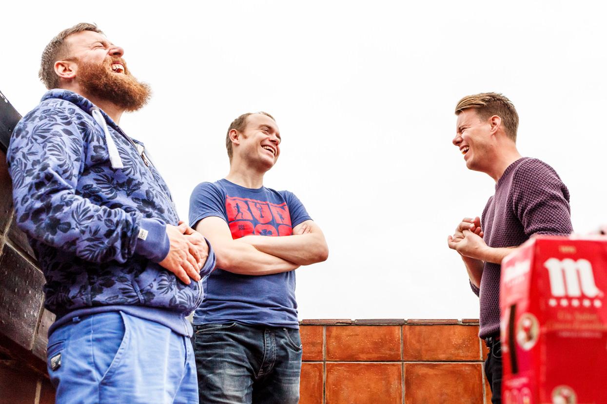 Novio riendo con amigos de boda en Donostia