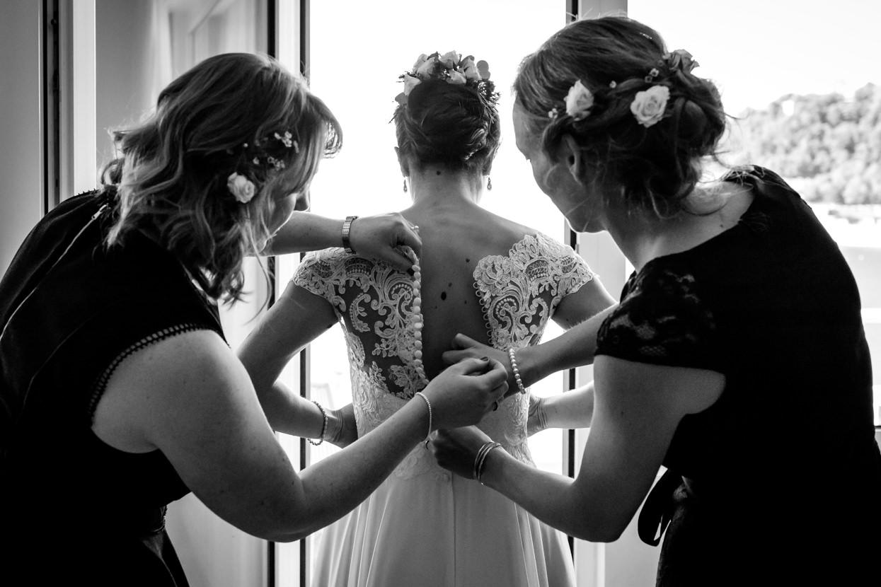 Preparativos de boda. Amigas colocan el vestido de novia