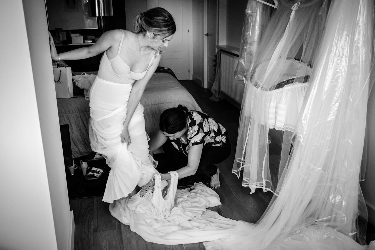 Hermana ayuda a la novia a ponerse el vestido de boda