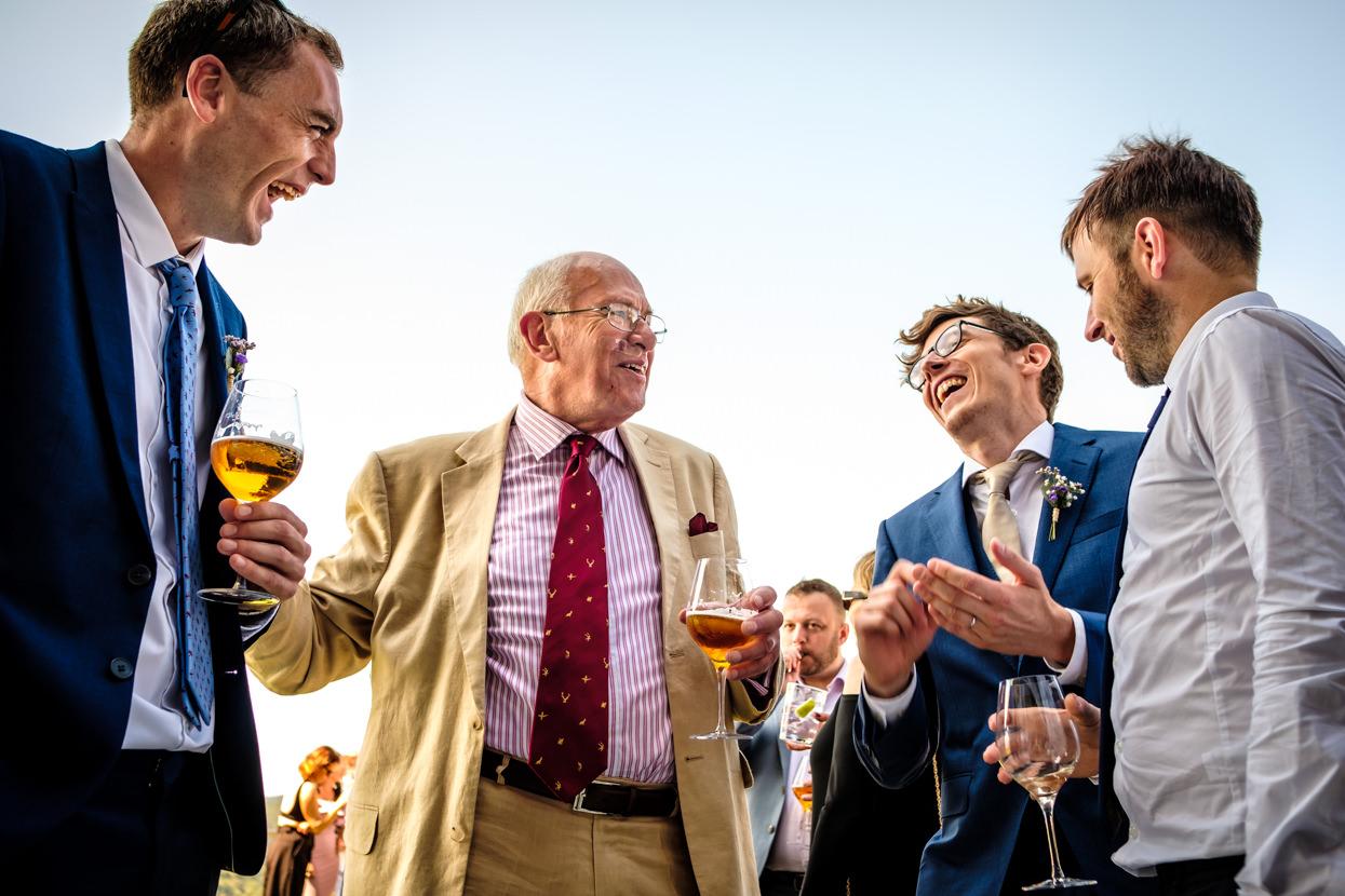 Novio ríe con amigos invitados de boda