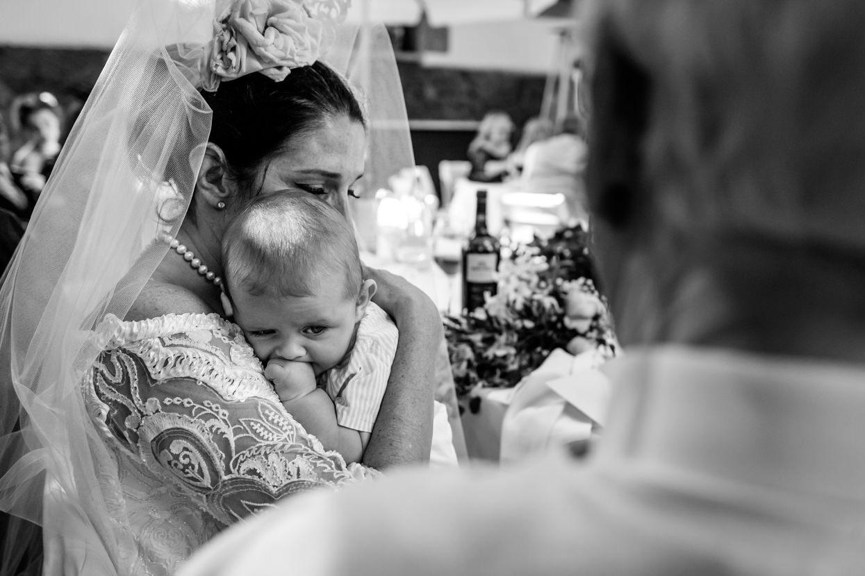novia de boda abraza a bebé