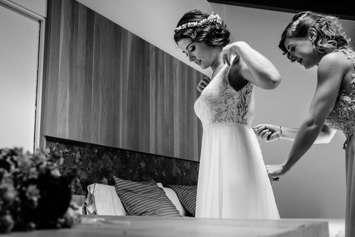 Hermana ayuda a novia a ponerse el vestido.